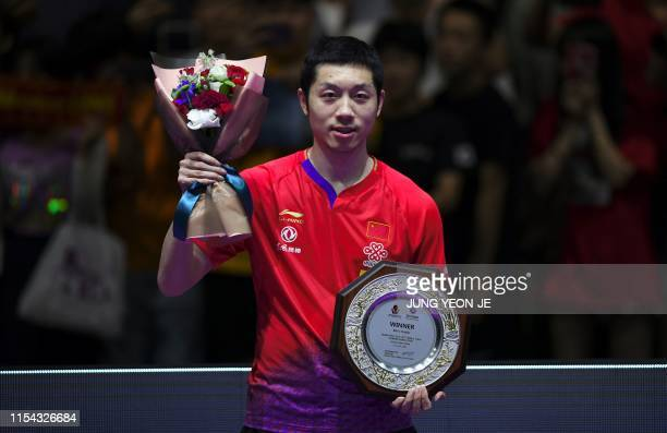 China's Xu Xin poses after winning the men's singles final match against compatriot Ma Long during the 2019 ITTF World Tour Korea Open table tennis...