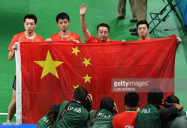 China's Xu Xin Zhang Jike coach Liu Guoliang and Ma Long hold the national Chinese flag as they celebrate winning the men's team gold medal table...
