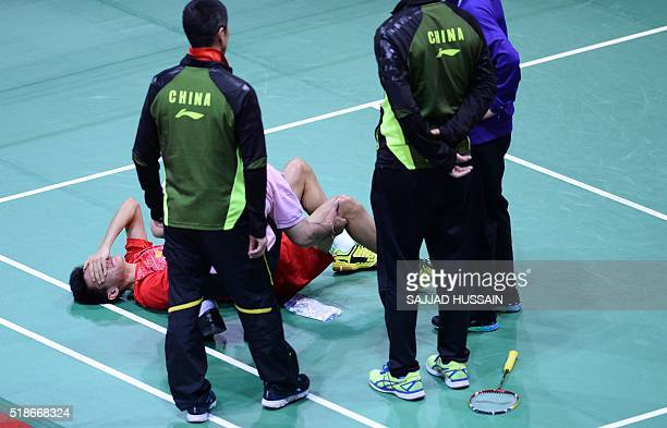 China's Xue Song is attended by coaches as he lies injured on the court during his men's singles semifinal match against Japan's Kento Momota at the...