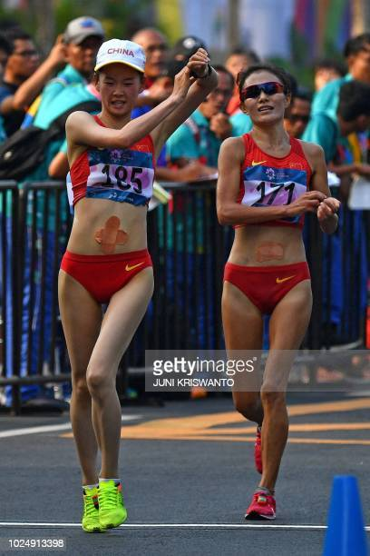 China's Yang Jiayu and China's Qieyang Shijie approach the finish line in the women's 20km walk race competition during the 2018 Asian Games in...