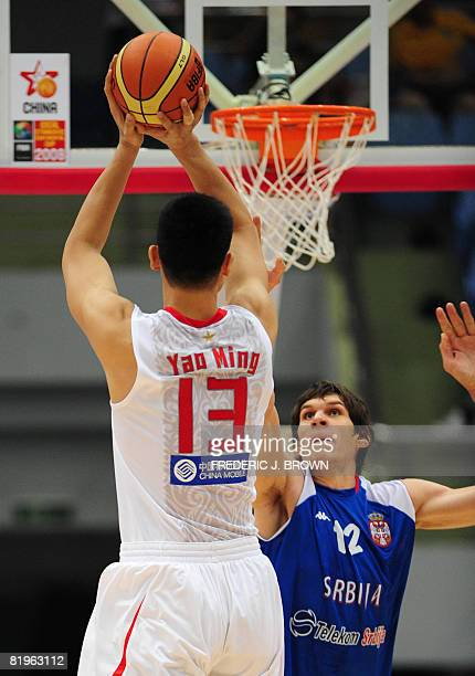 China's Yao Ming shoots under pressure from Serbia's Boban Marjanovic during their Stankovic Cup game in Hangzhou on July 17 2008 China leads Serbia...