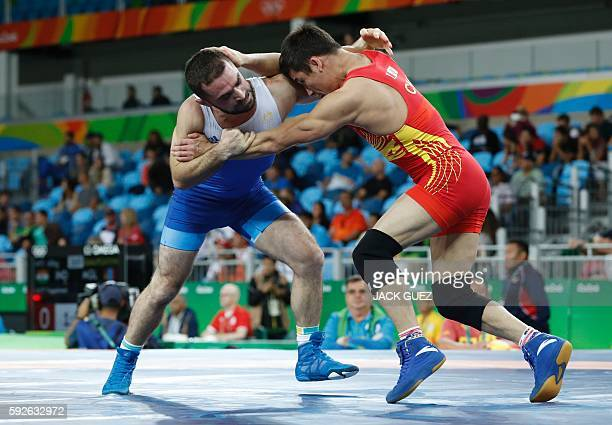 China's Yeerlanbieke Katai wrestles with Australia's Sahit Prizreni in their men's 65kg freestyle qualification match on August 21 during the...
