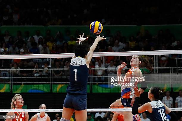 China's Yuan Xinyue blocks the ball in front of the Netherlands' Yvon Belien during the women's semifinal volleyball match between China and the...