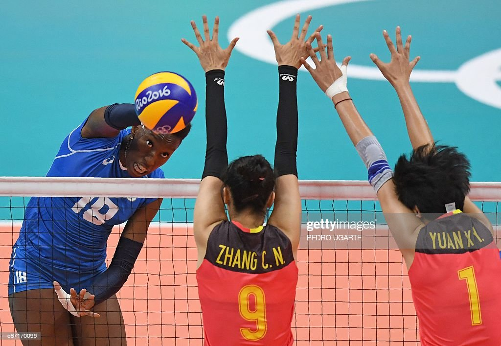 China's Zhang Changning (C) and China's Yuan Xinyue (R) attempt to block Italy's Paola Ogechi Egonu during the women's qualifying volleyball match between China and Italy at the Maracanazinho stadium in Rio de Janeiro on August 8, 2016, during the 2016 Rio Olympics. / AFP / PEDRO