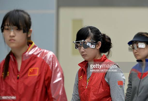China's Zhang Mengyuan and compatriots Zhou Qingyuan and Guo Wenjun compete during the women's 10m air pistol individual final of the 2014 Asian...