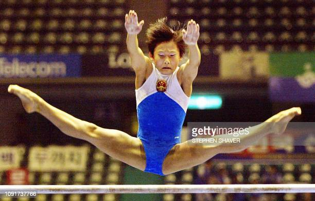 China's Zhang Nan performs on the uneven bars during the women's apparatus finals for the 14th Asian Games in Busan 04 October 2002 Zhang won gold...
