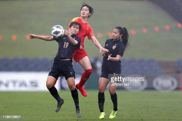 China's Zhang Xin and Thailand's Ploychompoo Somnonk and Nutwadee Pram-Nak challenge for the ball during the women's Olympic football tournament...