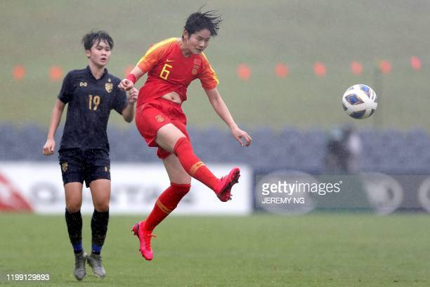Chinas Zhang Xin heads the ball in front of Thailand's Ploychompoo Somnonk during the women's Olympic football tournament qualifier match between...