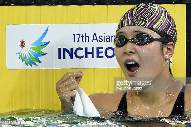 China's Zhang Yuhan reacts after her victory in the final of the women's 400m freestyle swimming event during the 17th Asian Games at the Munhak Park...