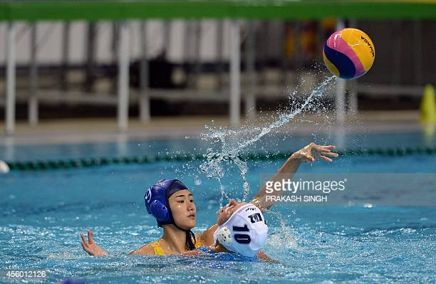 China's Zhao Zihan is challenged for the ball by Kazakhstan's Marina Gritsenko in their women's waterpolo single round robin match at the Dream Park...