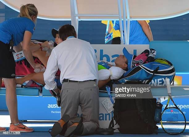 China's Zheng Jie receives treatment during her women's singles match against Australia's Casey Dellacqua on day five of the 2014 Australian Open...