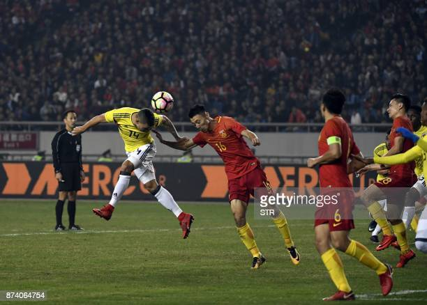 China's Zheng Zheng heads the ball next to Colombia's Andres Uribe during their international friendly football match in Chongqing southwest China on...