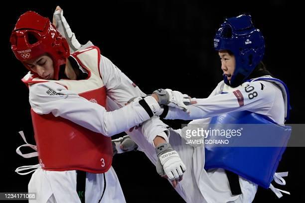 China's Zhou Lijun and Refugee Olympic Team's Kimia Alizadeh Zenoorin compete in the taekwondo women's -57kg quarter-final bout during the Tokyo 2020...