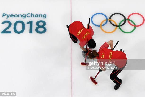 China's Zhou Yan and Liu Jinli brush the ice in front of the stone during the curling women's round robin session between China and Denmark during...
