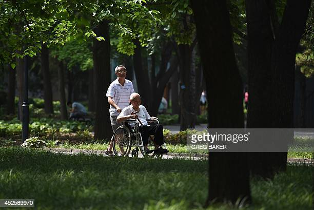 ChinasocialhealthcaredemographicsFEATURE by Carol HUANG This photo taken on June 29 2014 shows an elderly man being wheeled through a park in Beijing...