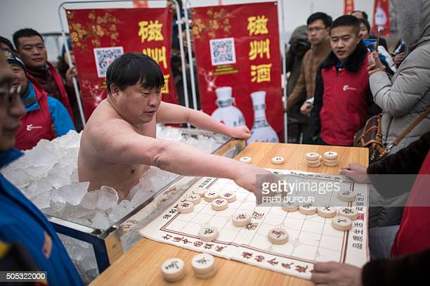Chinasportwinterswimmingoffbeat by Tom HANCOCK Cui Deyi known as 'Polar Bear' plays mahjong while being in a box filled with ice in Handan Hebei...