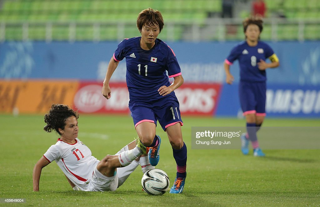 Chinatsu Kira of Japan competes for the ball with Sama'a Samir Hamad Khraisat of Jordan during the Women's Football Group B match between Japan and Jordan at Namdong Asiad Rugby Field during day -1 of the 17th Asian Games on September 18, 2014 in Incheon, South Korea.