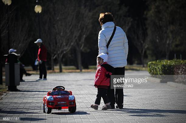 ChinaUShealthsurrogacyFEATURE by FELICIA A family walk along a road at a park in Beijing on November 26 2013 For decades China has been a top...