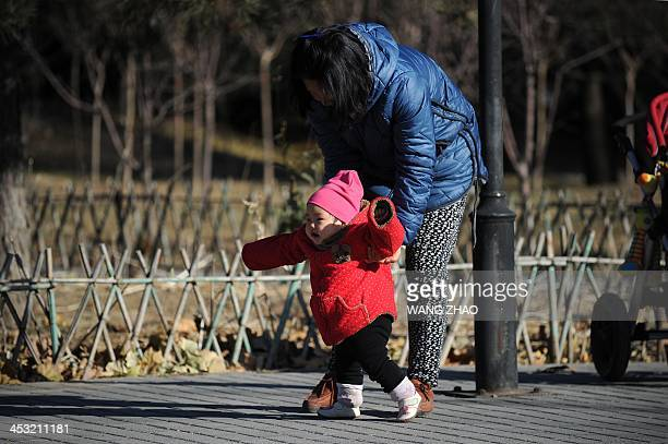 ChinaUShealthsurrogacyFEATURE by FELICIA A woman and child walk at a park in Beijing on November 26 2013 For decades China has been a top destination...