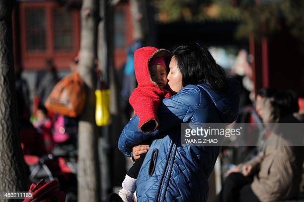 ChinaUShealthsurrogacyFEATURE by FELICIA A woman kisses a child at a park in Beijing on November 26 2013 For decades China has been a top destination...