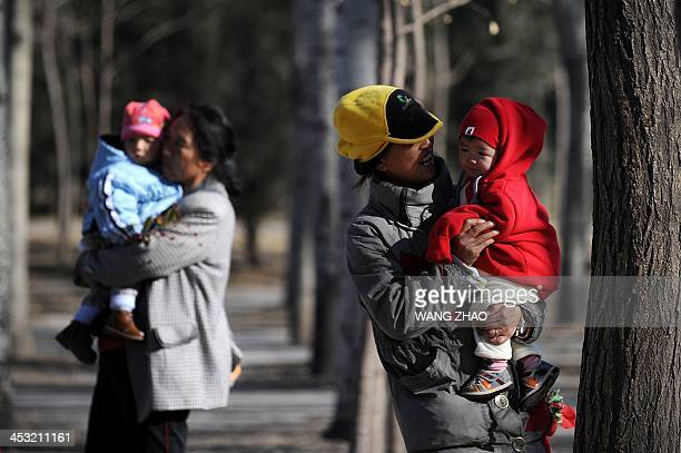 ChinaUShealthsurrogacyFEATURE by FELICIA Two Chinese families are seen at a park in Beijing on November 26 2013 For decades China has been a top...