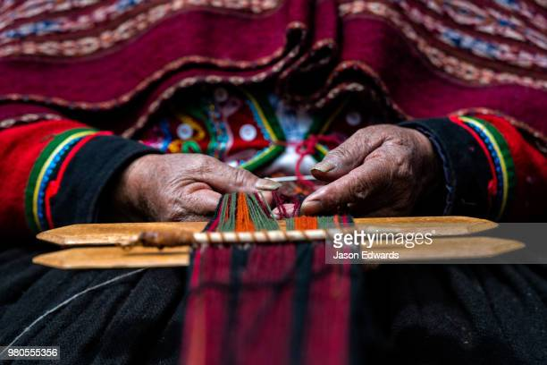 the weathered and hardened hands of an elderly quechua woman weaving llama wool. - cultura peruana fotografías e imágenes de stock