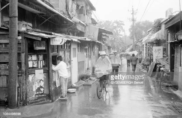 Chine juin 2002 La ville de Pékin et sa population Ici scène de rue sous la pluie dans un vieux quartier de Beijing