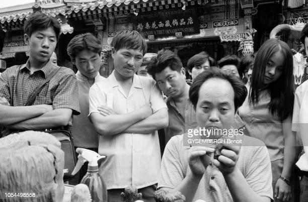 Chine juin 2002 La ville de Pékin et sa population Ici un artiste de rue modelant des visages en terre sous le regard des passants