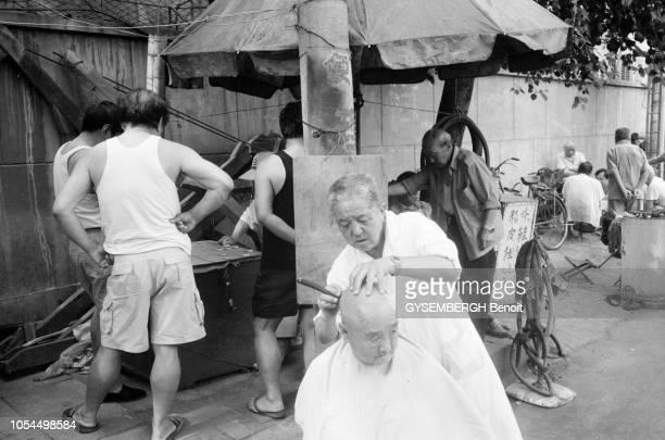 Chine juin 2002 La ville de Pékin et sa population Ici un coiffeur de rue derrière lequel des hommes jouent une partie d'échecs chinois