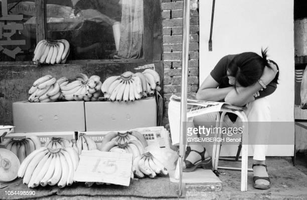 Chine juin 2002 La ville de Pékin et sa population Ici une vendeuse de bananes dormant sur sa chaise