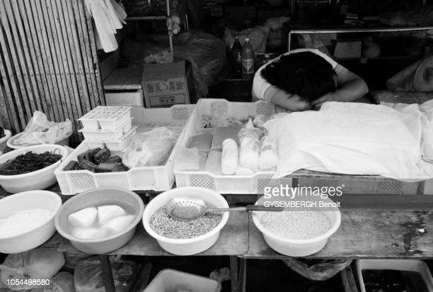 Chine juin 2002 La ville de Pékin et sa population Ici vendeur dormant sur son stand dans un marché populaire de Beijing