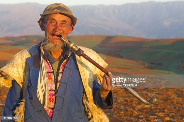 Chine province du Yunnanmunicipalite de Kumming district de Dongchuan terres rougesvillage de Guoditang cultures en terrasses berger paysan qui fume...