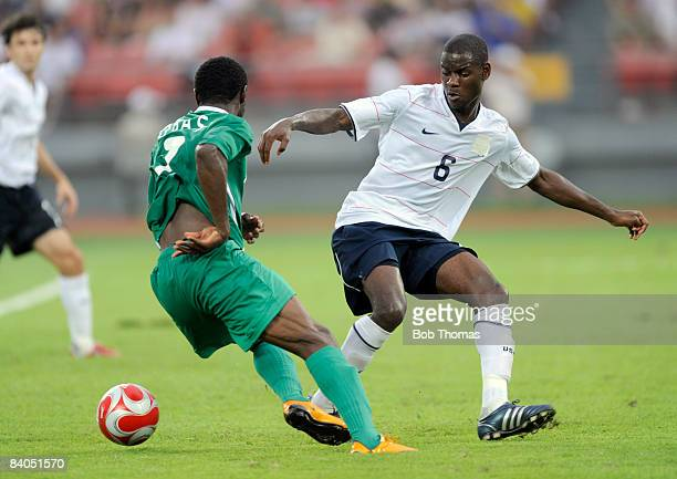 Chinedu Ogbuke Obasi of Nigeria with Maurice Edu of the United States during the Men's First Round Group B match between Nigeria and the United...