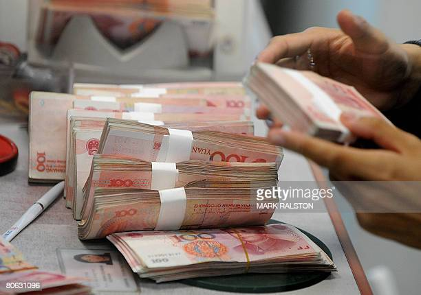 Chinese 100 Yuan notes are counted at a bank in Shanghai on April 11 2008 China's central bank set the yuan at 6992 against the USD the first time...
