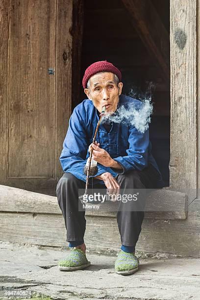 Chinese 94 year old senior man smoking pipe at homedoor