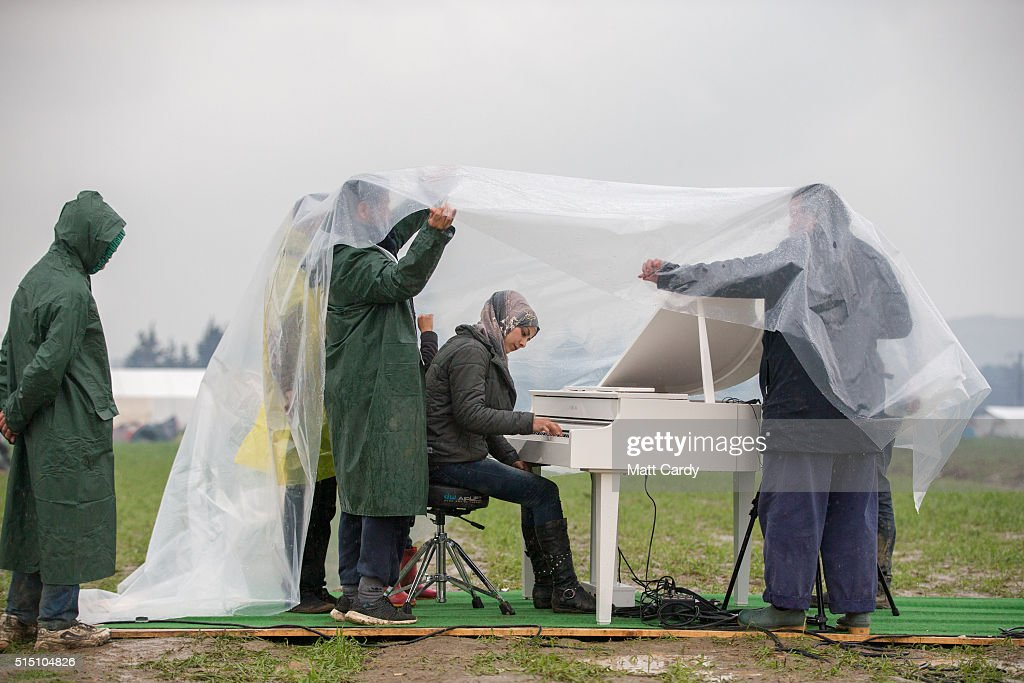 Chinese activist and artist Ai Weiwei (R) holds a sheet of plastic covering Syrian pianist Nour Al Khzam as she plays the piano for the first time in three weeks at the Idomeni refugee camp on the Greek Macedonia border on March 12, 2016 in Idomeni, Greece. The decision by Macedonia to close its border to migrants on Wednesday has left thousands of people stranded at the Greek transit camp. The closure, following the lead taken by neighbouring countries, has effectively sealed the so-called western Balkan route, the main migration route that has been used by hundreds of thousands of migrants to reach countries in western Europe such as Germany. Humanitarian workers have described the conditions at the camp as desperate, which has been made much worse by recent bouts of heavy rain.