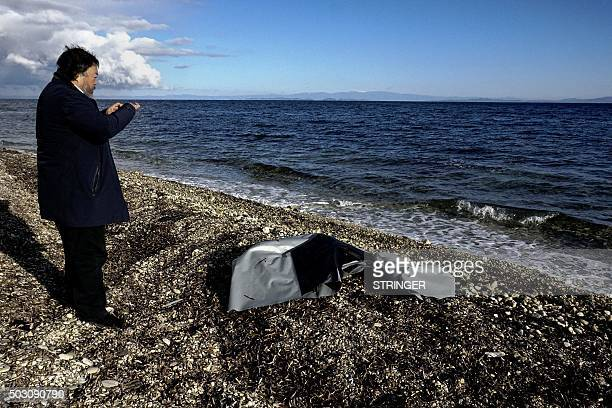 Chinese activist and artist Ai Weiwei takes a picture of the rest of a rubber boat washed up a beach near the town of Mytilene on the Greek island of...