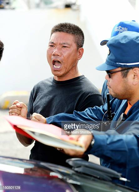 A Chinese activist leaves Japan Coast Guardfs patrol boat at Naha Port to be transferred to district police after landing on the disputed Uotsuri...