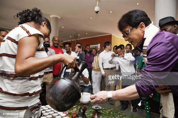 Chinese actor Jackie Chan takes a cup of traditional Ethiopian coffee during a welcoming ceremony at the Haile Resort on the sidelines of an event...