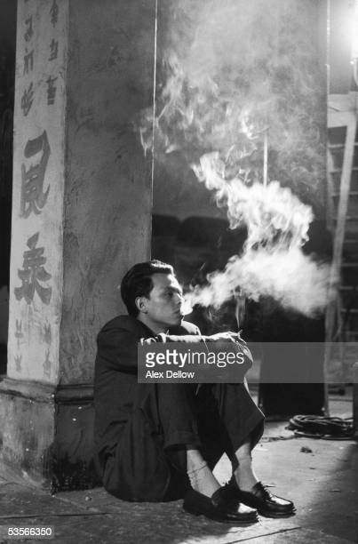 A chinese actor relaxing on the set of Leslie Norman's wartime film 'The Night My Number Came up' 1955
