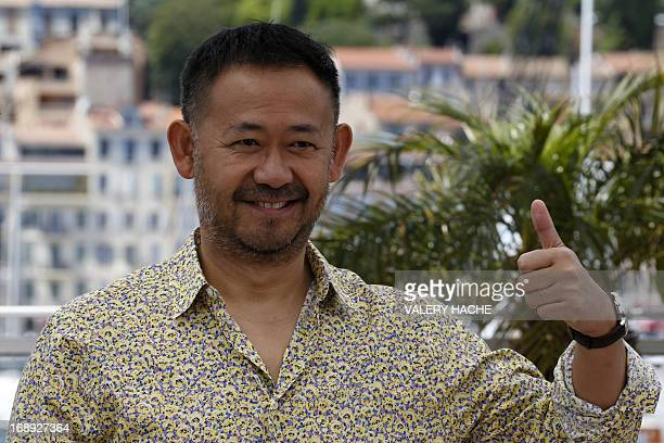 Chinese actor Wu Jiang gives a thumbsup on May 17 2013 while posing during a photocall for the film 'Tian Zhu Ding' presented in Competition at the...