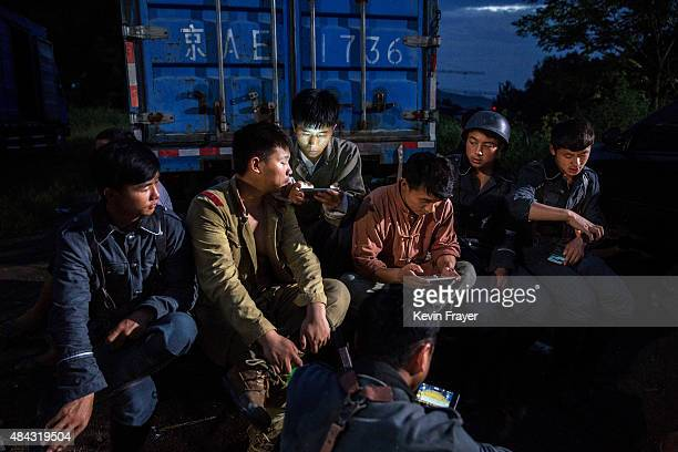 Chinese actors watch films on their mobile phones during a break in the filming of a battle segment in a series set during the second SinoJapanese...