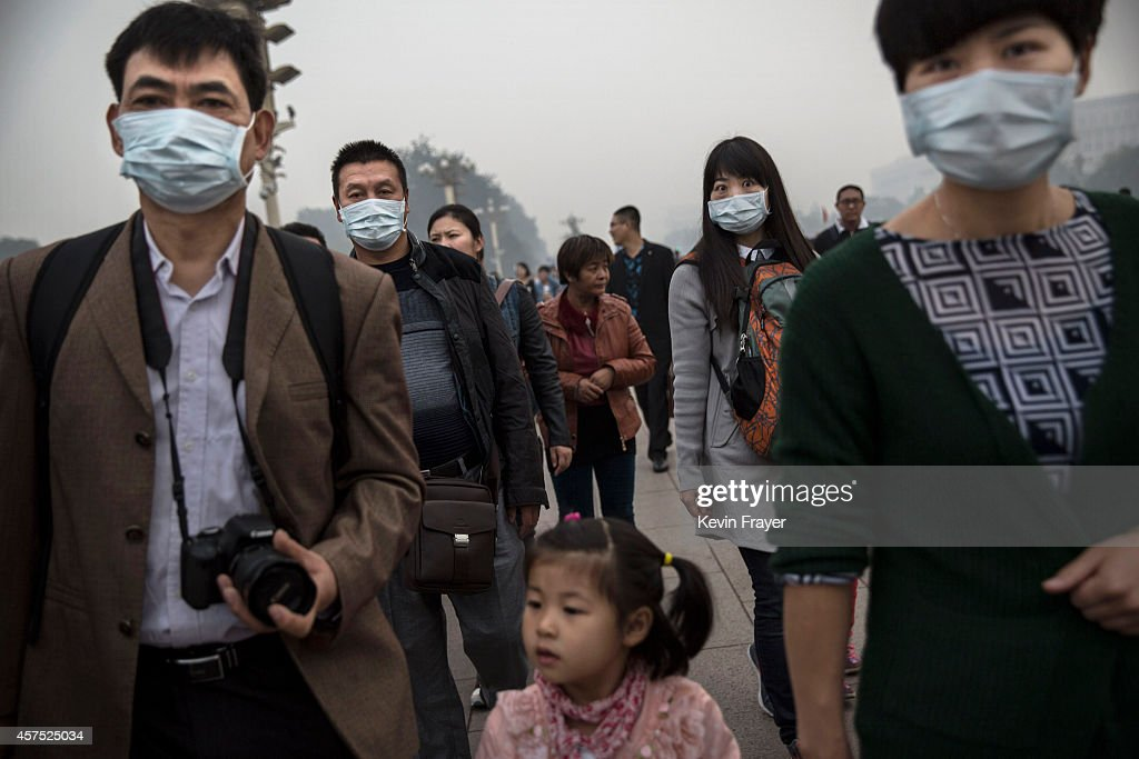 Chinese adults wear masks on a smoggy day near Tiananmen Square October 19, 2014 in Beijing, China.