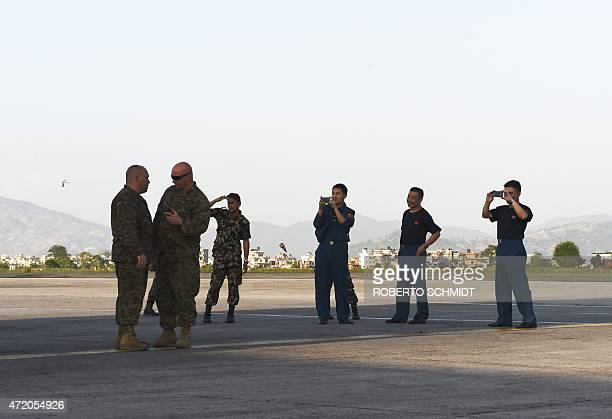 Chinese air force officers use their phones to take photos of two US officers standing in front of a US C17 transport plane in Kathmandu on May 3...