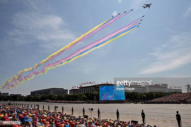 Chinese air force planes and fighter jets release smoke as they fly over Tiananmen Square and the Forbidden City during a military parade on...