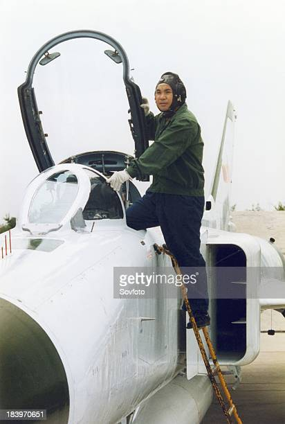A Chinese Air Force test pilot climbing into the cockpit of a Shenyang J8 II fighter China 1990