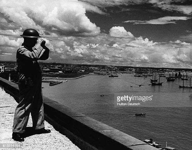 A Chinese air raid warden mans the roof of a building overlooking the city of Singapore during World War II