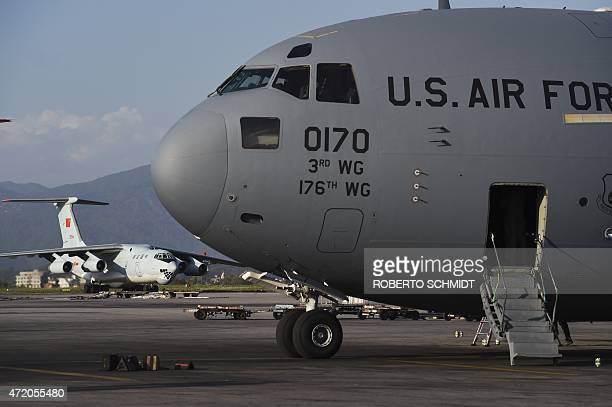 A Chinese airforce transport plane taxis on the runway near a US military C17 transport plane at Kathmandu's international airport on May 3 2015 as...