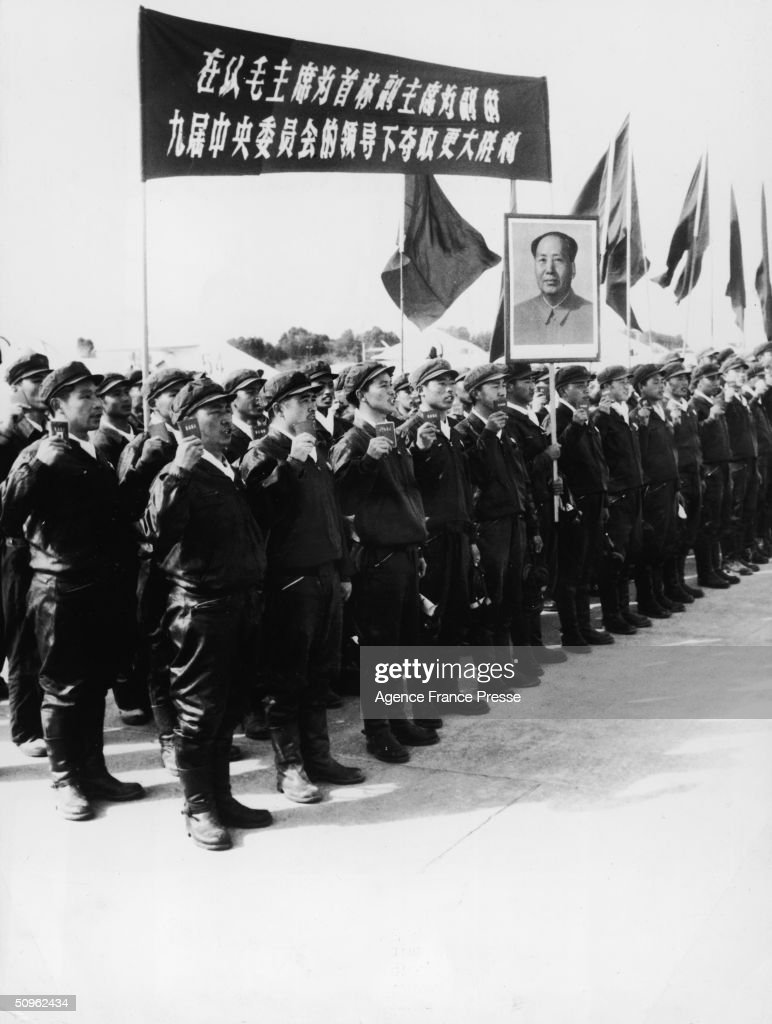 Chinese airmen stand in formation, wearing leather uniforms, holding a banner, a Mao Tse Tung portrait and copies of the 'Little Red Book,' China May 27, 1969.