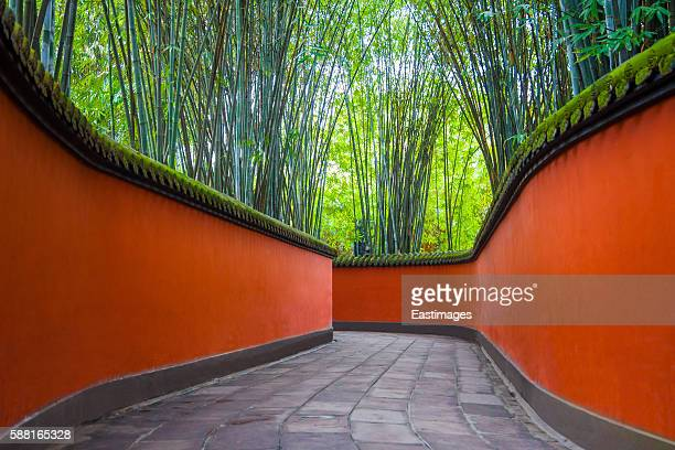 Chinese alley with red wall and green bamboo forest